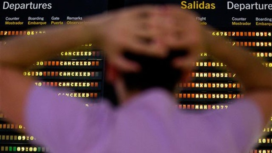 May 11: A passenger looks at a flight departure screen showing all flights canceled at the international airport in Seville, Spain.