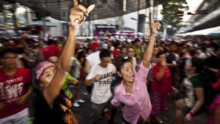 May 13: Anti-government demonstrators dance to rock music while attending an early morning rally in Bangkok, Thailand. Thai authorities prepared Wednesday to cut water, electricity and food supplies to anti-government demonstrators camped in central Bangkok, turning to siege tactics after a compromise offer failed to end their protest.