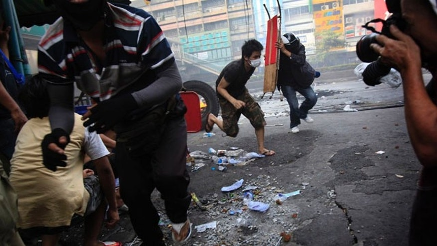 Anti-government protesters run for cover as Thai soldiers fire shots at them at an intersection on Saturday May 15, 2010 in Bangkok, Thailand.
