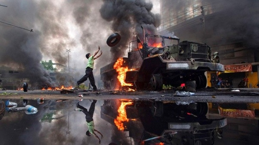 May 16: An anti-government protester 'Red Shirt' throws a tire toward a burned truck as the violence in central Bangkok continues.