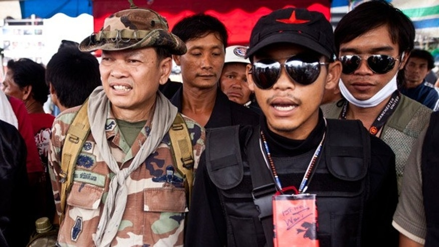 "May 1: Thai Maj. Gen. Khattiya Sawasdiphol, left, also known as ""Seh Daeng"", a rogue commander for the anti-government ""Red Shirts,"" gathers with others in Bangkok."