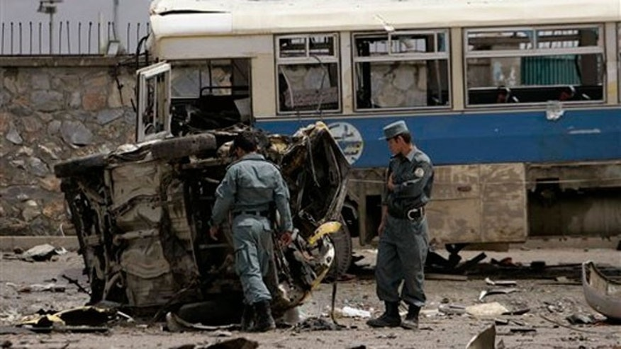 May 18: Afghan policemen look at the mangled remains of a vehicle after an attack in Kabul, Afghanistan.