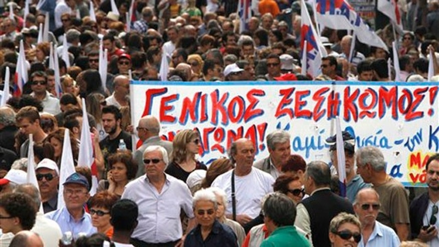 "May 20: Demonstrators hold a banner which reads in Greek ""General uprising'' during a march organized by a Communist-backed labor union, in central Athens."