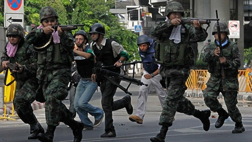 May 19: Thai soldiers run to take cover near the Red Shirts' barricade in Bangkok.