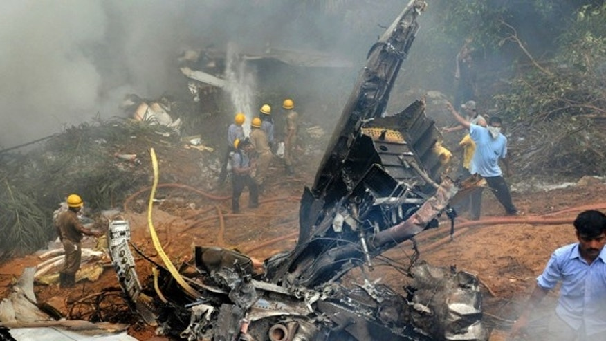 May 22, 2010: Indian firefighters and rescue personnel try to extinguish the flames from the wreckage of an Air India plane that crashed in Mangalore, in the southern Indian state of Karnataka.
