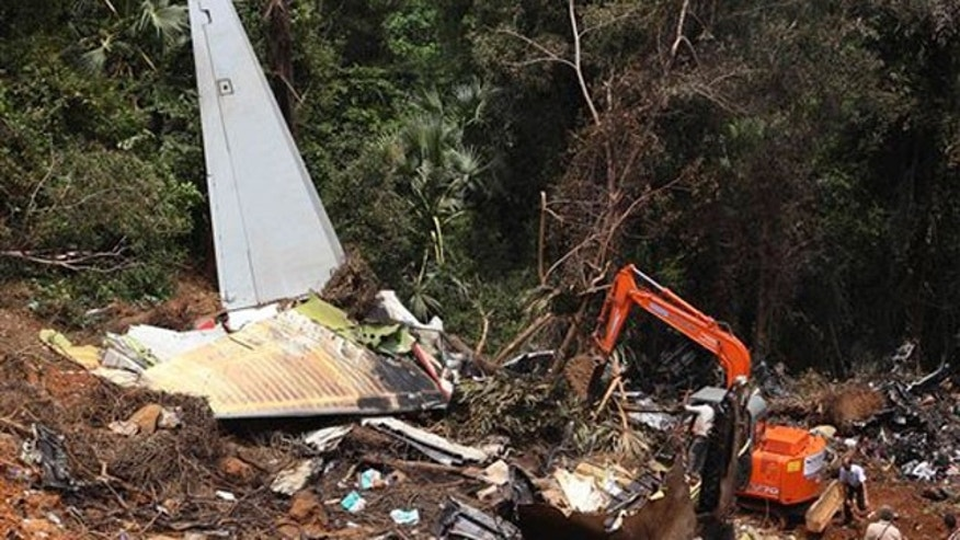 May 23: An earth remover cleans the site of the Air India Express plane crash in Mangalore, India.