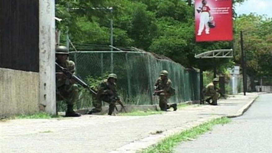 May 25: Jamaican army troops take cover during operations in Kingston, Jamaica, in search for reputed drug kingpin.