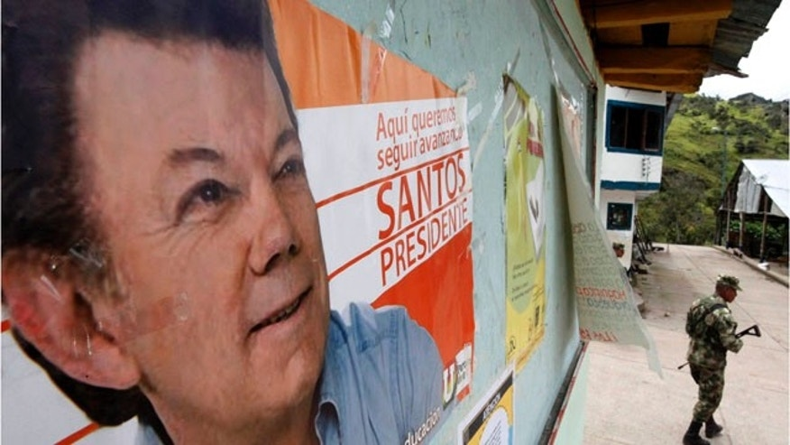 May 26: A soldier patrols under a poster of Juan Manuel Santos, the presidential candidate of the Social National Unity Party, in Nazareth, south of Bogota, The government has tightened the security ahead of May 30 presidential election.