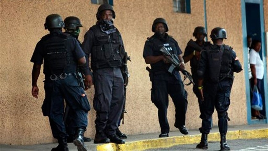May 26: Police officers stand guard near the emergency room entrance of the national hospital in Kingston, Jamaica.