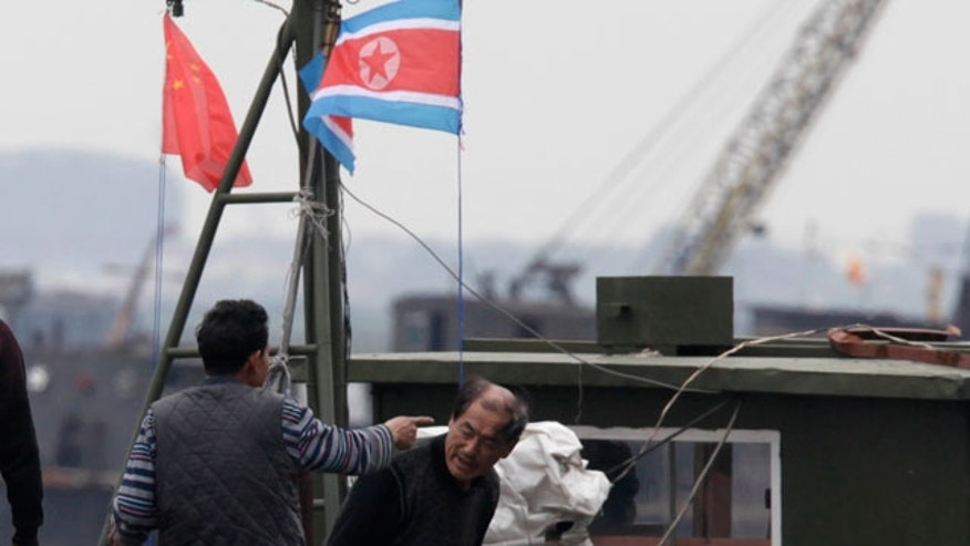 A man gestures towards another onboard a boat marked with both Chinese and North Korean flags along the Yalu river near Dandong in northeastern China's Liaoning province on Saturday, May 29, 2010. Top South Korean military commanders in Seoul discuss how to counter North Korean provocations as the leaders of South Korea, China and Japan head to the South Korean southern island of Jeju for a summit expected to focus on the sinking of a warship blamed on North Korea.