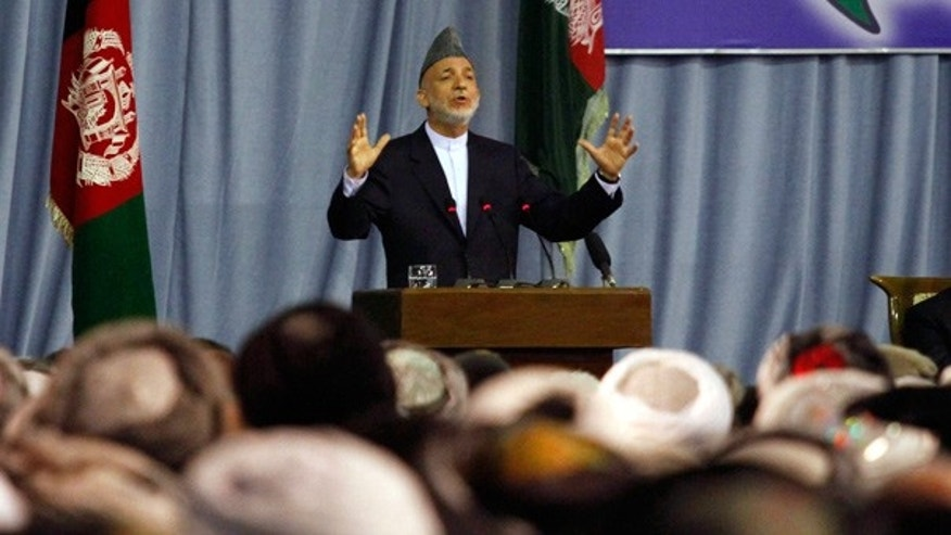 June 2: Afghan President Hamid Karzai asks attendees of the peace jirga to take their seats after hearing an explosion during his opening address in Kabul.