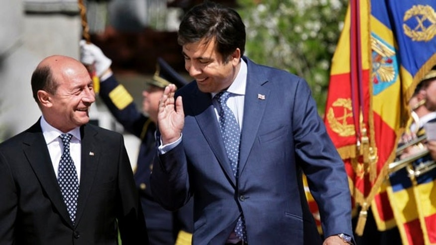 June 2: Georgian President Mikhail Saakashvili and Romanian President Traian Basescu walk past an honor guard during the welcoming ceremony at the Cotroceni Presidential Palace, Bucharest, Romania.