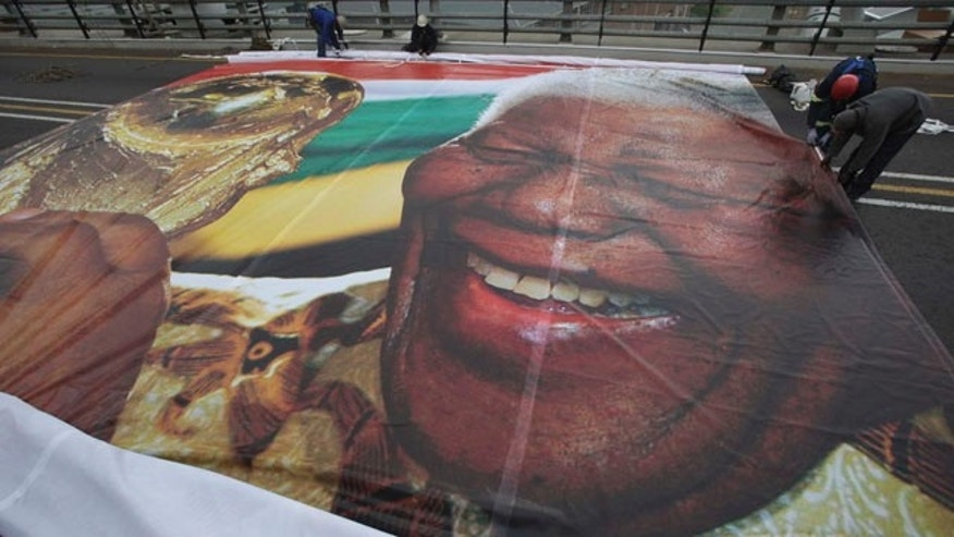 May 30: Workers prepare to hang an image of former President Nelson Mandela with the World Cup trophy on the Mandela bridge leading to downtown Johannesburg. (AP)