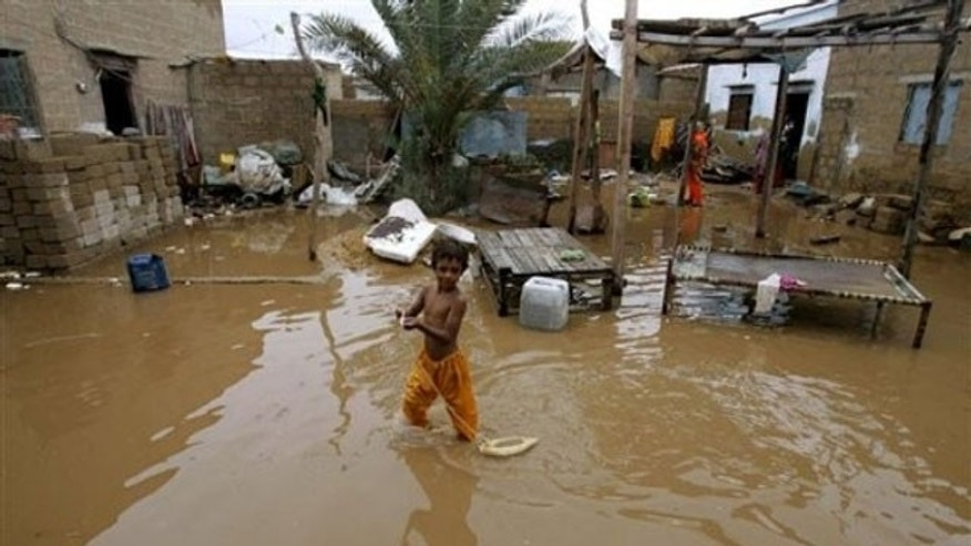 June 6: A child walks through flood waters caused by torrential rains outside his home in Karachi, Pakistan. An approaching tropical storm triggered torrential rains in Pakistan's largest city and surrounding areas on Sunday, collapsing mud houses and submerging roads (AP).