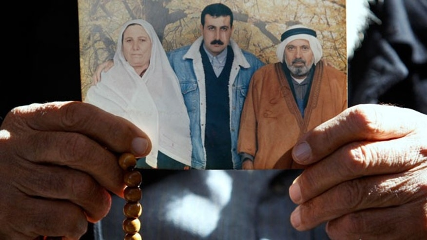 In this Jan. 29, 2010 file photo the father of Palestinian militant Mahmoud al-Mabhouh, who was killed in Dubai in January, holds up a family photo showing al-Mabhouh, center, at their home in the Jebaliya refugee camp, northern Gaza Strip. Polish authorities have arrested an alleged Mossad spy from Israel wanted in connection with the slaying of a Hamas agent in Dubai, the German federal prosecutor's office said Saturday June 12, 2010.