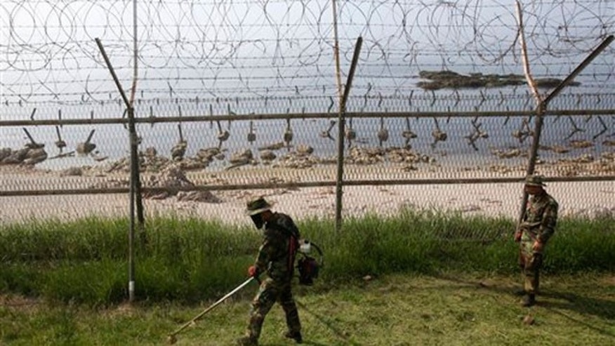 June 15: South Korean Marines work along the fence on Baengnyeong Island, South Korea, near the border with North Korea.
