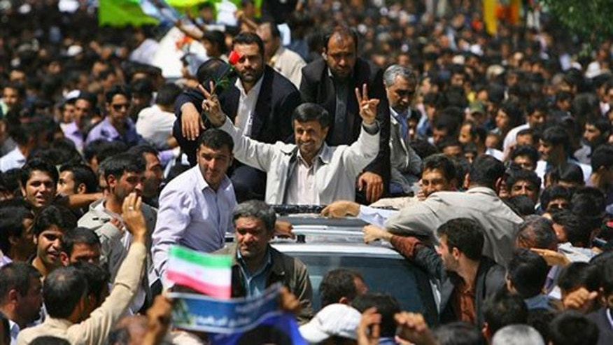 June 16: Escorted by his bodyguards, Iranian President Mahmoud Ahmadinejad, center, flashes the victory sign to supproters as he arrives in the city of Shahr-e-Kord. Ahmadinejad says Tehran supports a dialogue with the outside world but that world powers must first be punished for the latest round of U.N. sanctions imposed on Iran.