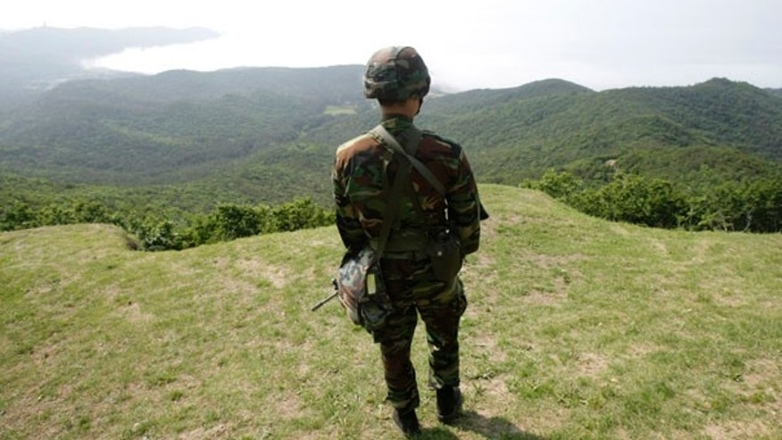June 15: A South Korean Marine looks across the border into North Korea as he stands guard on Baengnyeong Island, South Korea.