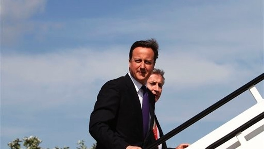 June 24, 2010: Britain's Prime Minister David Cameron center, walks to board a plane at London's Heathrow airport, to depart for Canada, for his first summits of the G8 and G20 groups of major world powers as Prime Minister.