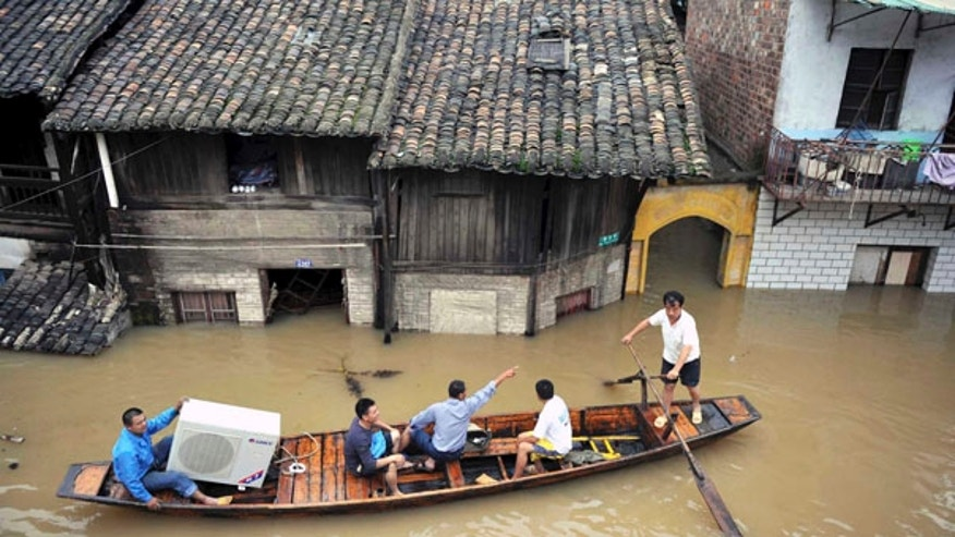 June 24: Llocal residents transfer their belongings on a boat in Xiangtan county, in central China's Hunan province.