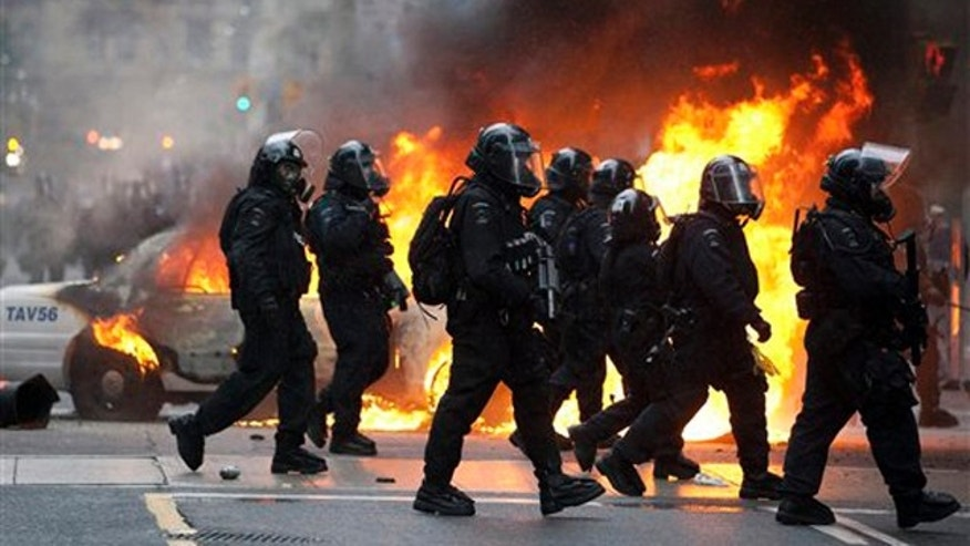 June 26, 2010: Riot police walk by a burning police car in downtown Toronto during anti G20 protests.