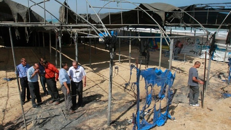 June 28: United Nations employees inspect the damage at a U.N. children's summer camp on the beach of Zawaida town in the central Gaza Strip. Two dozen masked men vandalized the summer camp early Monday, burning and slashing tents, toys and a plastic swimming pool, in a second such attack in a month.