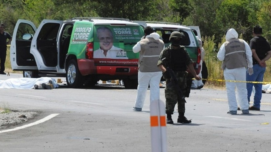 June 28: Army soldiers guard the crime scene as investigators work where the candidate for governor of the state of Tamaulipas, Rodolfo Torre, was ambushed by unidentified gunmen near the city of Ciudad Victoria, Mexico. (AP)