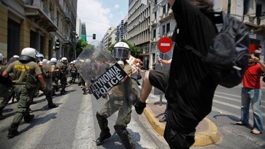 A demonstrator kicks a riot policeman during clashes in central Athens on Tuesday, June 29, 2010. Some 16,000 people took part in two separate demonstrations, the second of which turned violent as stone-throwing youths fought with riot police. Public services shut down across Greece Tuesday as workers walked off the job in a new nationwide general strike that disrupted public transport, left hospitals operating on emergency staff and pulled all news broadcasts off the air. (AP Photo)