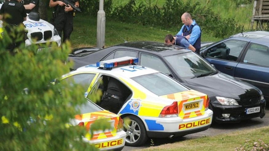 July 6: Armed police check a  black Lexus car and secure the area around it in Rothbury, northeast England. The car is believed to have been driven by Raoul Moat, the man police are searching for in connection with the of shooting his ex-girlfriend, killing her new boyfriend and seriously wounding a police officer.