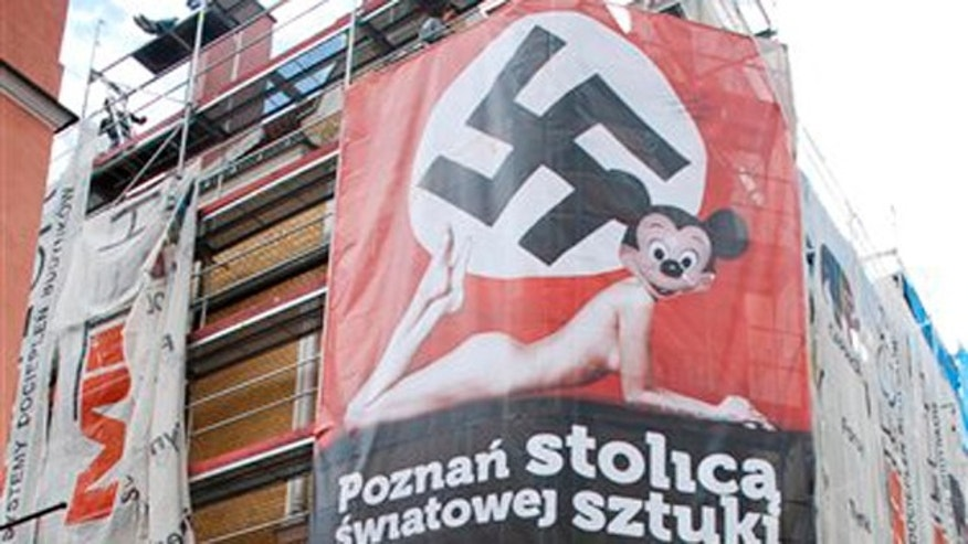This image  taken June 19, 2010 shows a  worker walking below a huge poster advertising a contemporary art exhibition blending images of a Nazi swastika with that of a nude female body and Mickey Mouse in Poznan, western Poland.