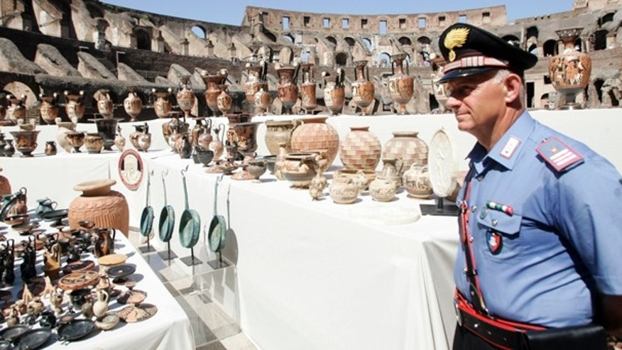 July 16: A police officer looks at some of the hundreds of ancient artifacts recovered during an operation against looted art, at the Colosseum in Roma. (AP)