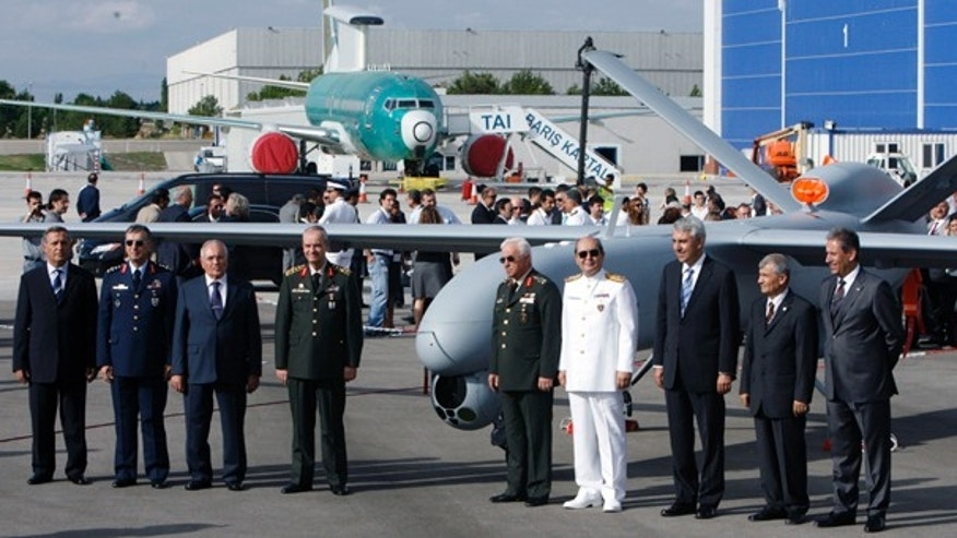 July 16: Turkish army commanders and other officials pose in front of turkey's first drone airplane called Anka or Phoenix during a roll out ceremony at the TAI-Turkish Aerospace Space Industries Inc., near Ankara, Turkey. (AP)