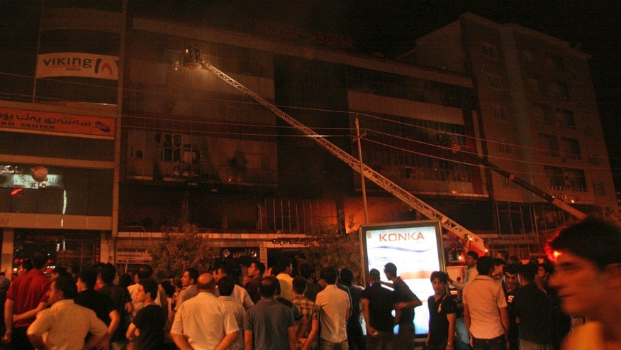 July 16: Iraqis gather as firefighters respond to a fire in a five-story hotel in Sulaimaniyah, 160 miles northeast of Baghdad. Some of the victims appeared to have died as they jumped from the windows to escape the blaze.