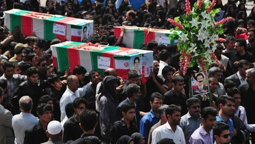 During a funeral ceremony, people carry flag-draped coffins of the victims of two bomb blasts in the city of Zahedan, 940 miles (1570 kilometers) southeast of the capital Tehran, Iran, Saturday, July 17, 2010. A Sunni insurgency called Jundallah, which has carried out several other bombings in the southeast over the past few years, claimed responsibility for Thursday's blasts, which killed 27. (AP Photo/Fars News Agency, Ali Azimzadeh)
