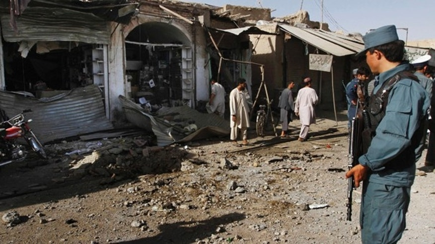 July 20: An Afghan policeman stands guard at the site of a homicide bomibng in Kandahar city, south of Kabul, in Afghanistan.