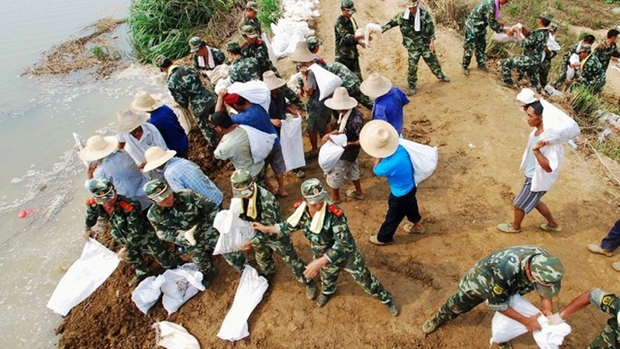 In this Tuesday, July 20, 2010 photo, paramilitary police and workers move sandbags to fortify the Fanghu dyke in Pengze county, in central China's Jiangxi province. Flooding this year has killed 701 people, left 347 missing and caused tens of billions of dollars in damage, the worst toll across the board that China has seen in a decade, a senior Chinese official said Wednesday. (AP Photo) **  CHINA OUT **