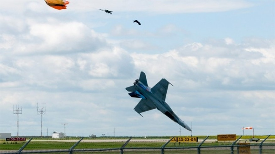 July 23: Pilot Capt. Brian Bews parachutes to safety as his a CF-18 fighter jet plummets to the ground during a practice flight at the Lethbridge County Airport for the weekend airshow in Lethbridge, Alberta, Canada.