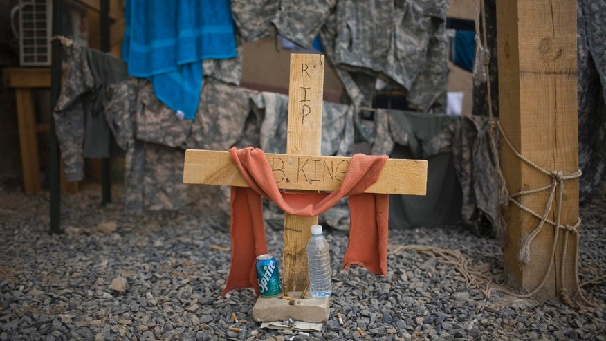 July 24: A cross sits below the guard tower where a U.S. soldier was killed while standing guard duty in Kandahar, Afghanistan.