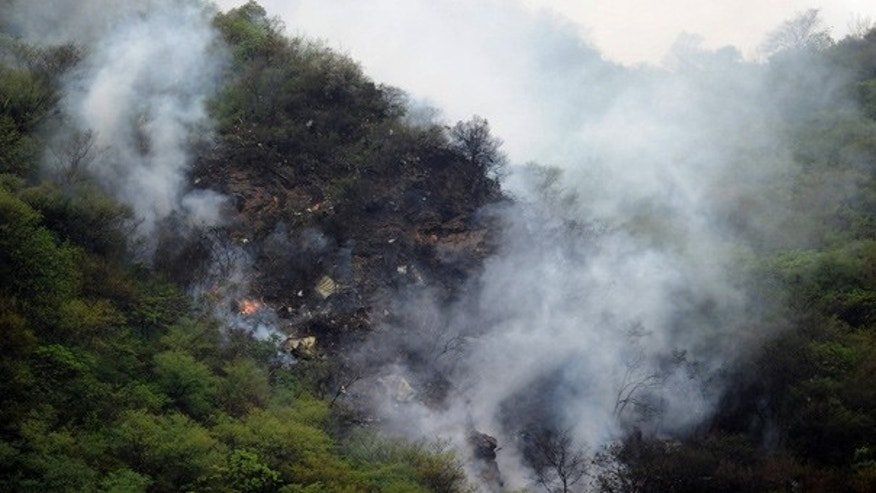 July 28: Fire and smoke rises from the wreckage of a passenger plane is seen in the Margalla Hills of Islamabad.