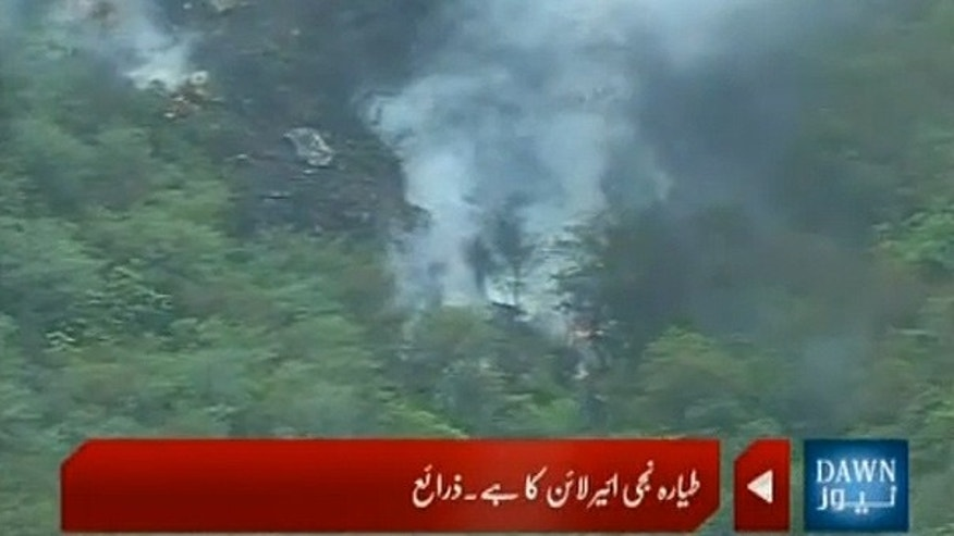 July 28: A television screen capture shows the crashed passenger jet on a hillside in Islamabad, Pakistan.