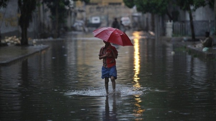 July 27: A boy wades through a flooded Karachi street as monsoon rains swept across Pakistan.