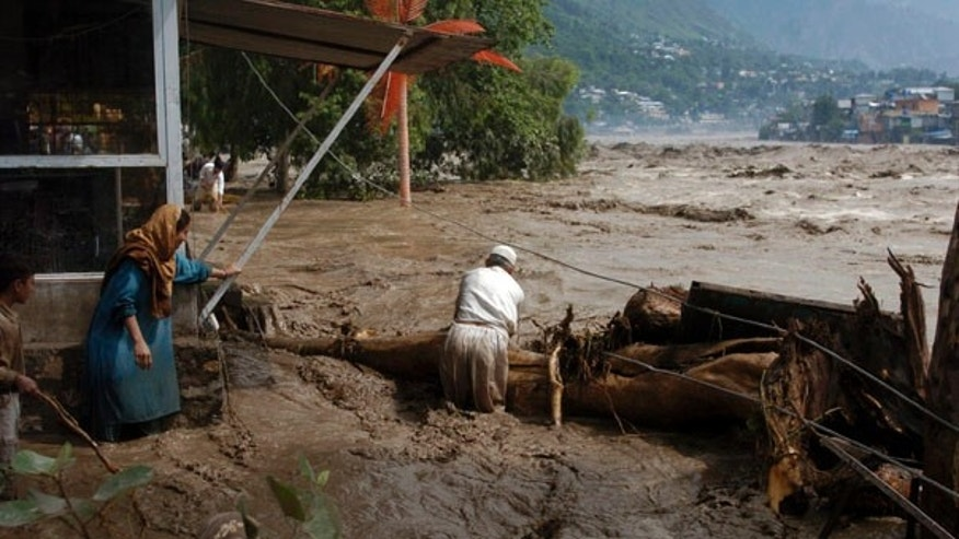 July 30: Pakistani villagers try to catch trees float in the flooded Nelum river in Muzaffarabad, the capital of Pakistani Kashmir.