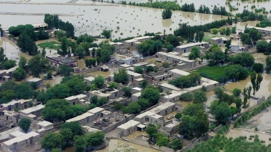 July 31: Houses are submerged in water due to heavy flooding in Dera Ismail Khan, Pakistan. The death toll continues to rise, and thousands of people are trapped in rural villages.