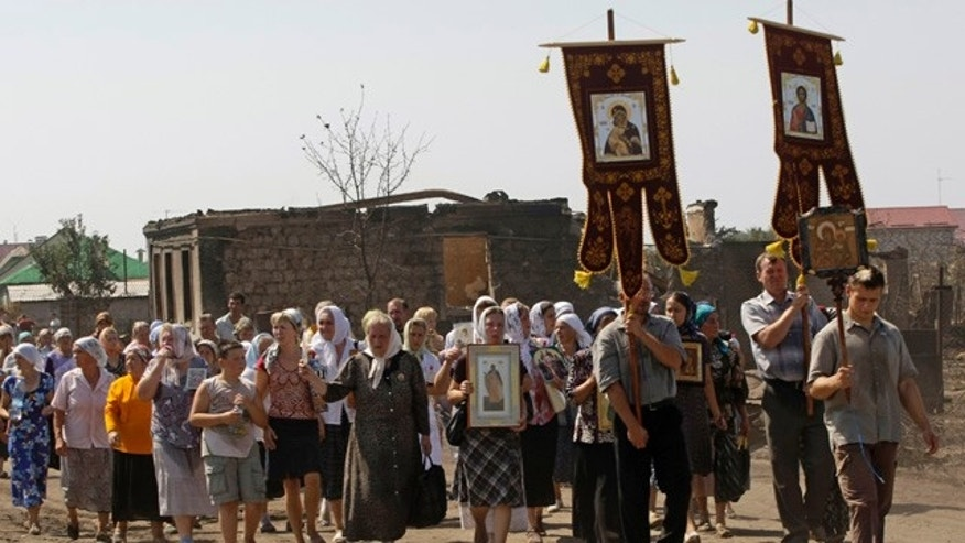 Aug. 1: People carry icons during a religious procession in front of the ruins of burnt out houses after a forest raged out of control in a suburb of the town of Voronezh some 294 miles south of Moscow.