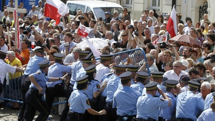 Aug. 3: Supporters of late Polish President Lech Kaczynski scuffle with municipal guards as they try to break a barrier in front of the Presidential palace in Warsaw. Authorities failed to move a cross commemorating Poland's late leader Lech Kaczynski from in front of the presidential palace after fierce protests by Roman Catholic groups and Kaczynski's followers.