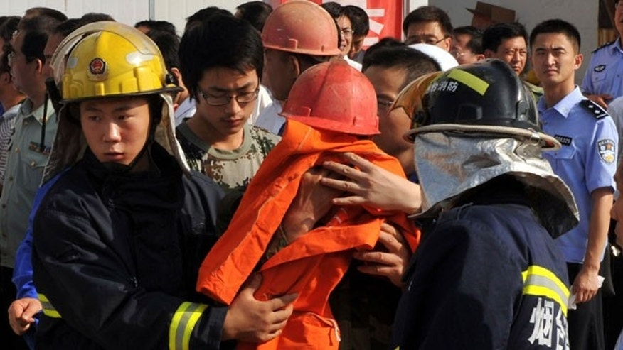 In this photo released by China's Xinhua News Agency, rescuers escort rescued miner onto an ambulance at the site of fire at Luoshan Gold Mine in Zhaoyuan, Yantai City, east China's Shandong Province Saturday, Aug. 7, 2010. A fire broke out at the Luoshan Gold Mine run by Lingnan Mining Co. Ltd. on Friday.