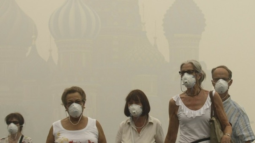 Aug. 6: Tourists wear protective face masks as they walk along the Red square in thick smog in Moscow, Russia. The city was shrouded Friday by a dense smog that grounded flights at international airports and seeped into homes and offices, as wildfires that have killed 50 people nationwide continued to burn.