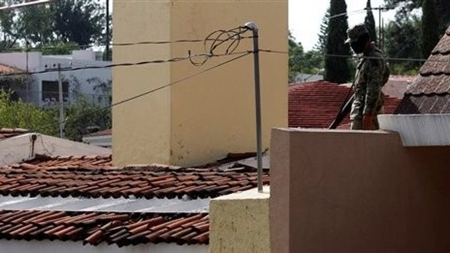 July 30: A soldier stands guard on the roof of the house where, according to Mexico's Defense Ministry, a top leader of the Sinaloa cartel, Ignacio Coronel Villareal, was killed in Guadalajara, Mexico. President Felipe Calderon launched a military offensive against organized crime in 2006. (AP)