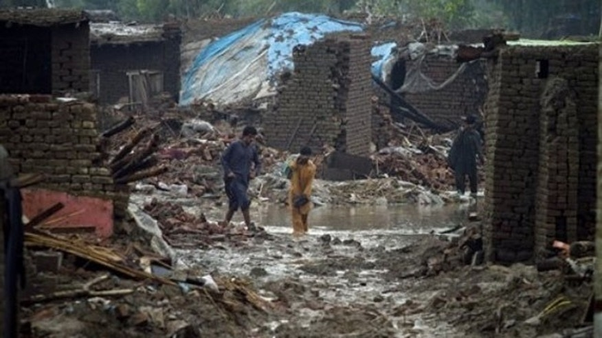 Aug. 8: Flood effected people walk past the rubble the collapsed houses in Azakhel near Nowshera, Pakistan. The country will need billions of dollars to recover from its worst floods in history, further straining a country already dependent on foreign aid to prop up its economy and back its war against Islamist militants, the U.N. said (AP).