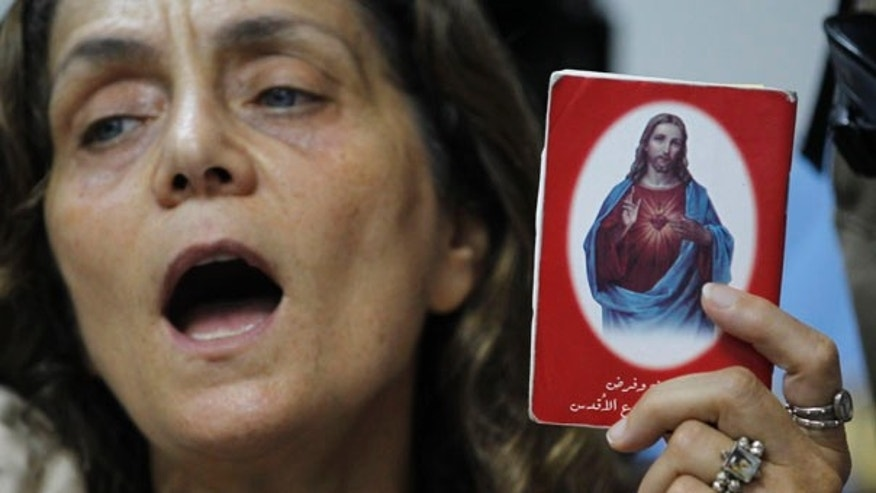 Aug. 13: A Christian woman prays and holds a picture of Jesus as she protests against the airing of a program about Jesus on two Shiite Muslim TV stations in Lebanon.